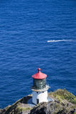 Makapuu Lighthouse on Ohau Island in Hawaii and passing boat Stock Photo