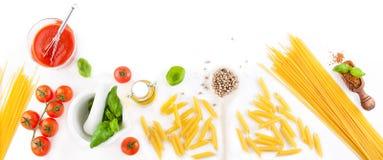Makaronów składniki pomidory, oliwa z oliwek, czosnek, włoscy ziele, świeży basil i spaghetti na białej deski tle -, Obrazy Royalty Free