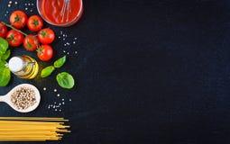 Makaronów składniki pomidory, oliwa z oliwek, czosnek, włoscy ziele, świeży basil, sól i spaghetti na czarnym kamiennym tle -, Fotografia Stock