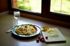 Makaron Carbonara z kraciastym Parmeza?skim serem i czere?niowymi pomidorami dekoruj?cymi z arugula, W?oski lunch zdjęcie stock