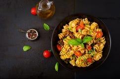 Makaron Fusilli z pomidorami, wołowiną i basilem w czarnym pucharze na stole, Obraz Stock