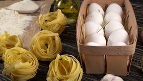 Makaron, jajka, czosnek, olej i mąka na drewnianym tle, zbiory
