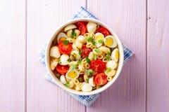 Makaron sałatka z przepiórek jajkami, mozzarellą, czereśniowymi pomidorami i kaparami w pucharze na purpurowym drewnianym tle, obrazy royalty free