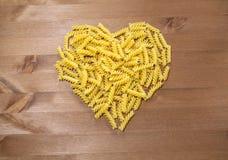 Makaron spirale rozpraszać na drewnianym stole zdjęcie royalty free
