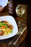 Makaron z mięsem, kumberlandem i pomidorami na talerzu, fotografia royalty free