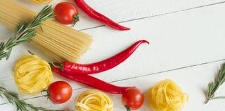 Makaron z pomidorem, chili pieprze, rozmaryny na bielu stole Obrazy Stock