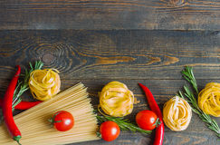 Makaron z pomidorem, chili pieprze, rozmaryny na drewnianym stole Obrazy Royalty Free
