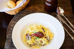 Makaron z rozciekłym serem i kawałkami mięso na talerzu fotografia royalty free