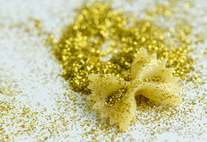 Makaroni bow shape in tinsels on white background Royalty Free Stock Image