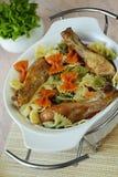 Makaronier med stekta kycklingarna som dekoreras av grönsaker Fotografering för Bildbyråer