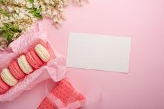 Makarons in een doos op een lichtrose achtergrond met een gift, flatlays, met een lege ruimte voor een inschrijving of gelukwense royalty-vrije stock fotografie