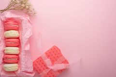 Makarons in een doos op een lichtrose achtergrond met een gift, flatlays, met een lege ruimte voor een inschrijving of gelukwense stock foto