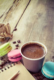 Makarons, espressokop en schetsboek op houten plattelander Stock Afbeeldingen