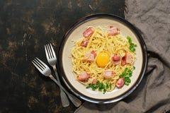 Makaronu carbonara z parmesan, bekon, surowy yolk na ciemnym nieociosanym tle na widok obraz royalty free