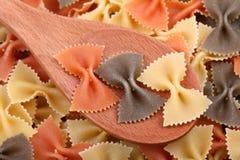 Makaronu farfalle tricolore w drewnianej łyżce Zdjęcie Stock