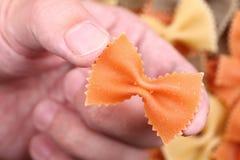 Makaronu farfalle w palcach Zdjęcie Royalty Free