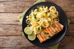 Makaronu fetuccini z cheddaru serem i piec na grillu łososiem na plat Fotografia Stock