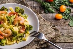 Makaronu linguine z garnelami i brokułami w talerzu na drewnianym tle Zdjęcia Royalty Free