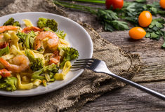 Makaronu linguine z garnelami i brokułami w talerzu na drewnianym tle Zdjęcie Stock