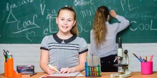 Make изучая химию интересную Воспитательная концепция эксперимента Одноклассники девушек изучают химию Микроскоп и стоковые фото