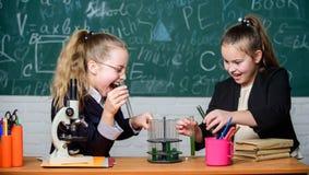 Воспитательная концепция эксперимента Микроскоп и пробирки на таблице Быть осторожным выполняющ химическую реакцию Основной стоковые фото