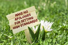 Make on apologies for setting high standards. On wooden sign in garden with white spring flower stock images