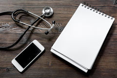 Make an appointment with doctor by cell phone dark wooden desk top view notebook mock up Stock Images