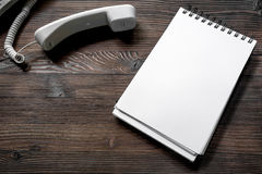 Make an appointment by phone dark wooden desk top view notebook mock up Royalty Free Stock Image