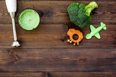 Make baby food at home. Puree with broccoli near immersion blender and toy on dark wooden background top view copy space. Make baby food at home. Puree with Stock Photos