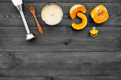 Make baby food at home. Puree with pumpkin near immersion blender and pacifier on dark wooden background top view copy. Make baby food at home. Puree with Royalty Free Stock Photography