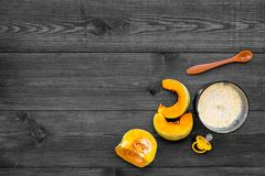Make baby food at home. Puree with pumpkin near immersion blender and pacifier on dark wooden background top view copy. Make baby food at home. Puree with Stock Photos
