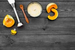 Make baby food at home. Puree with pumpkin near immersion blender and pacifier on dark wooden background top view copy. Make baby food at home. Puree with Royalty Free Stock Photos