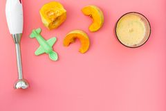 Make baby food at home. Puree with pumpkin near immersion blender, toy on pink background top view copy space. Make baby food at home. Puree with pumpkin near Stock Images