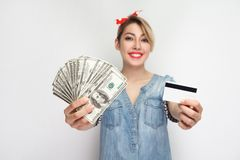 Make choice for usability cash or card. Young girl in casual blue denim shirt standing, demonstrate cash and credit card for. Choosing, toothy smile. indoor royalty free stock photo