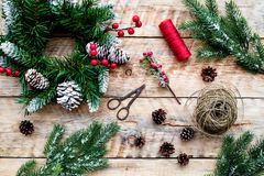 Make christmas wreath. Spruce branches, cones, threads, twine, sciccors on light wooden background top view.  royalty free stock photos