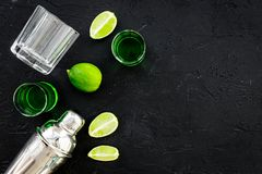 Make cocktail with absinthe. Shaker, shots, lime slices on black background top view space for text. Make cocktail with absinthe. Shaker, shots, lime slices on royalty free stock image