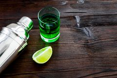Make cocktail with absinthe. Shaker, shots, lime slices on dark wooden background top view space for text. Make cocktail with absinthe. Shaker, shots, lime royalty free stock photos