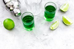 Make cocktail with absinthe. Shaker, shots, lime slices on grey background top view space for text. Make cocktail with absinthe. Shaker, shots, lime slices on royalty free stock images