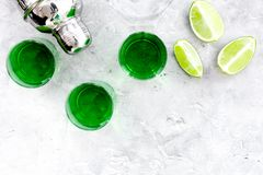 Make cocktail with absinthe. Shaker, shots, lime slices on grey background top view space for text. Make cocktail with absinthe. Shaker, shots, lime slices on royalty free stock photos
