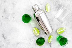Make cocktail with absinthe. Shaker, shots, lime slices on grey background top view space for text. Make cocktail with absinthe. Shaker, shots, lime slices on royalty free stock photo