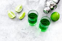Make cocktail with absinthe. Shaker, shots, lime slices on grey background top view space for text. Make cocktail with absinthe. Shaker, shots, lime slices on stock photo