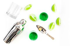 Make cocktail with absinthe. Shaker, shots, lime slices on white background top view.  royalty free stock photos