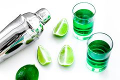 Make cocktail with absinthe. Shaker, shots, lime slices on white background top view.  royalty free stock photo