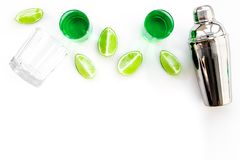 Make cocktail with absinthe. Shaker, shots, lime slices on white background top view copy space. Make cocktail with absinthe. Shaker, shots, lime slices on white stock image