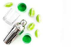 Make cocktail with absinthe. Shaker, shots, lime slices on white background top view copy space. Make cocktail with absinthe. Shaker, shots, lime slices on white royalty free stock photography