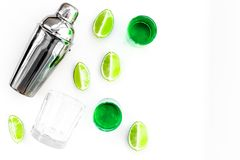 Make cocktail with absinthe. Shaker, shots, lime slices on white background top view copy space. Make cocktail with absinthe. Shaker, shots, lime slices on white stock photos