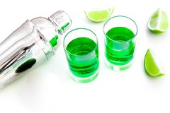 Make cocktail with absinthe. Shaker, shots, lime slices on white background top view copy space. Make cocktail with absinthe. Shaker, shots, lime slices on white stock images