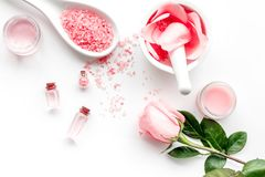 Make cosmetics with rose  oil. Mortar with rose petals and pestle on grey stone background top view copyspace Stock Images