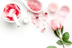 Make cosmetics with rose oil. Mortar with rose petals and pestle on white background top view copyspace. Make cosmetics with rose oil. Mortar with rose petals stock images