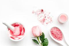 Make cosmetics with rose  oil. Mortar with rose petals and pestle on white background top view copyspace Royalty Free Stock Images